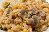 A meal of vegetable risotto with mushrooms, sweetcorn, carrot, green beans