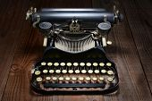Overhead shot of an antique typewriter on a rustic wood table.
