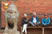 PATAN, NEPAL - APRIL 2014 : Nepalese men sitting next to a stone lion at Golden Gate, entrance to the Patan Museum in Patan, Nepal on 13 April 2014. Patan Museum is an old royal palaces.