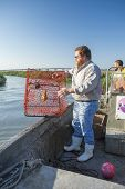 BEAUFORT, SOUTH CAROLINA, MAY 23, 2014: An unidentified commercial fisherman drops a crab trap into an estuary