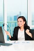 Asian Chinese business woman working in office controlling profit