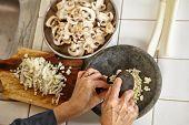 Hand crushing the garlic on mortar, slight movement blur on hand holding pebble to crush it.