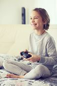 Child playing video game on tv in morning at parent's bedroom at home
