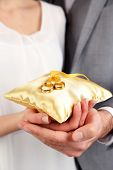 Man and woman holding wedding rings close up