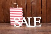 Sale with bags on wooden background
