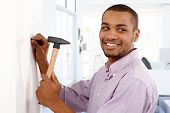 Happy young black man driving a nail to wall by hammer, smiling, looking away.