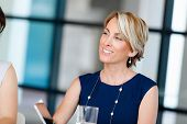 Businesswoman in blue dress sitting at meeting