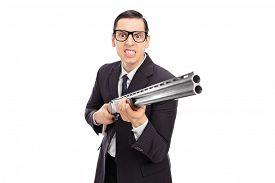 foto of shotgun  - Angry businessman holding a shotgun isolated on white background - JPG