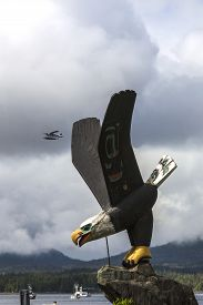 pic of float-plane  - Wooden sculpted Bald Eagle statue in Ketchikan with float plane in sky above