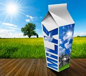 image of milk  - White packaging of fresh milk with text Milk in a countryside landscape with green grass and a tree on blue sky with clouds and sun rays - JPG