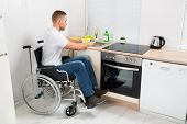 picture of disability  - Young Disabled Man On Wheelchair Washing Dishes In The Kitchen - JPG