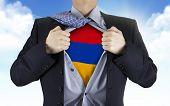picture of armenia  - businessman showing Armenia flag underneath his shirt over blue sky - JPG