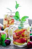 picture of infusion  - Jar delicious refreshing drink of peach fruits and plum with mint on wooden infused water - JPG