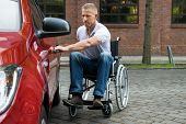 image of handicapped  - Portrait Of A Handicapped Man Sitting On Wheelchair Opening Door Of A Car - JPG