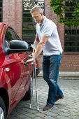 image of crutch  - Portrait Of A Handicapped Man With Crutches Opening Door Of A Car - JPG