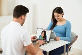 picture of video chat  - Couple Video Chatting With Each Other On Laptop And Digital Tablet - JPG