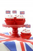 picture of red velvet cake  - Red white and blue theme cupcakes on red cake stand with UK Union Jack flags on white wood table for Queens Birthday and Great Britain party food - JPG