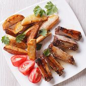 picture of baby back ribs  - Pork ribs potatoes and tomatoes on a plate close - JPG