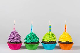 picture of sprinkling  - Four colorful cupcakes decorated with birthday candles and sprinkles - JPG