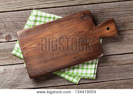 Cutting board over towel on wooden kitchen table. Top view