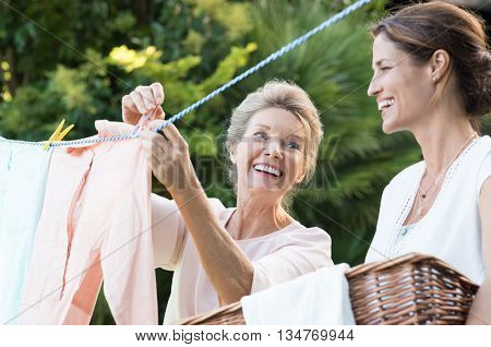 Older mother and young daughter hanging clothes outdoor to dry. Smiling daughter helping mother with