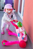 Little baby girl walking with the baby pusher poster