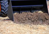 The Tractor Bucket Heats The Ground. Tractor Bucket, Front Loader In Actin. poster