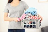 Woman holding plastic basket with clothes indoors. Laundry day poster
