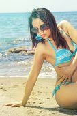 Sensual Bikini Woman On The Sea Beach With Sunglasses. A Woman In A Swimsuit And Sunglasses Sitting  poster