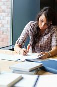Retrato de una bella estudiante escribir un ensayo en una biblioteca