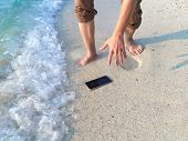Hands Of Young Asian Man Dropping Mobile Smart Phone On Tropical Sandy Beach. Accident And Insurance poster