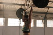 Strong Woman With Barbell Overhead Doing Exercise. Fit Female Athlete Lifting Heavy Weights. poster