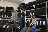 Young Male Mechanics With Car Tires In Automobile Service Center poster