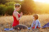 Mother Teaching Her Daughter To Practice Yoga Meditation poster