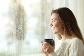 Happy Teen Holding A Mug Looking Through A Window At Home In A Rainy Day poster