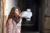 Vape E-cig. A Young Cute White Girl In Warm Scarf And Gloves Is Vaping An Electronic Cigarette In Th poster