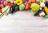 Different colorful vegetables arranged as a frame. Organic food. Wooden background. poster