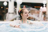 Little girl relaxing in a hot tub. Bubbly bath. Water park. Leisure activities. poster
