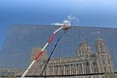 foto of cherry-picker  - A Red and White Cherry Picker and Glass Building with Reflection of Historic Building - JPG