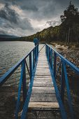 Mole (pier) On The Scandinavian Lake With Motorboat On Side And Misty Hills. Blue Wooden Bridge In F poster