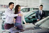 Cheerful Vietnamese Couple Choosing Car In Car Dealership poster