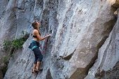 Climber Overcomes Challenging Climbing Route. A Girl Climbs A Rock. Woman Engaged In Extreme Sport.  poster