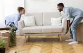 Moving Concept. Cheerful Afro Spouses Placing Couch Furnishing Empty Room In New House After Relocat poster