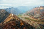 Vivid Multicolor Landscape Of Green Valley Among Big Rocky Mountains. Beautiful Highland Scenery Of  poster