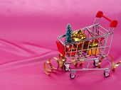 Christmas Tree In Shopping Cart On Background Of Shiny Pink Satin As Background, Silk Background, Ch poster