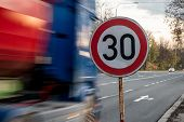 A Fast Driving Blue Speeding Truck With Motion Blur Effect Near The Traffic Sign Limiting The Maximu poster