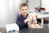Little Boy With An Inhaler (nebulizer) Makes The Procedure To His Toy, Bunny. Inhalation At Home For poster