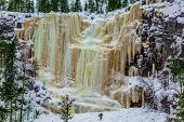 Man -  tourist climbs to frozen waterfall. Wall of frozen water. Lapland. The concept of photo and e poster