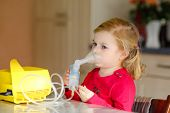 Little Toddler Girl Making Inhalation With Nebulizer At Home. Lovely Baby Holding The Device. Child  poster