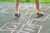 image of hopscotch  - Girl playing hopscotch outdoors with pink chalk - JPG